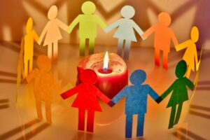 multicolored paper people around a candle